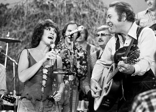 "Ruth Buzzi, left, veteran of TV's original ""Laugh-In,"" and host Roy Clark perform a rousing rendition of ""May the Bird of Paradise Fly up Your Nose"" with apologies to Little Jimmy Dickens during a taping of ""Hee Haw"" on Oct. 4, 1977."