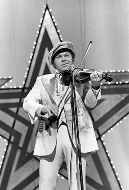 Co-host Roy Clark, who earlier won the Instrumental Group of the Year award with Buck Trent, performs during the CMA Awards show at the Grand Ole Opry House on Oct. 11, 1976.
