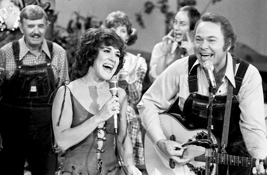"Ruth Buzzi, left, veteran of TV's original ""Laugh-In,"" and host Roy Clark perform a rousing rendition of ""May the Bird of Paradise Fly up Your Nose"" during a taping of ""Hee Haw"" on Oct. 4, 1977."