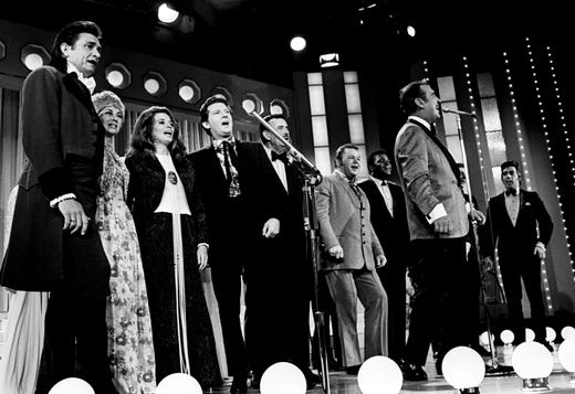 "Big winner Johnny Cash, left, joins other CMA award winners on the stage of the Ryman Auditorium to sing a chorus of ""This Land is Your Land"" at the end of the NBC live telecast of the CMA Awards show Oct. 15, 1969. Next to Cash are Tammy Wynette, June Carter Cash, Jerry Lee Lewis, Archie Campbell, Roy Clark, Charley Pride and Tennessee Ernie Ford."