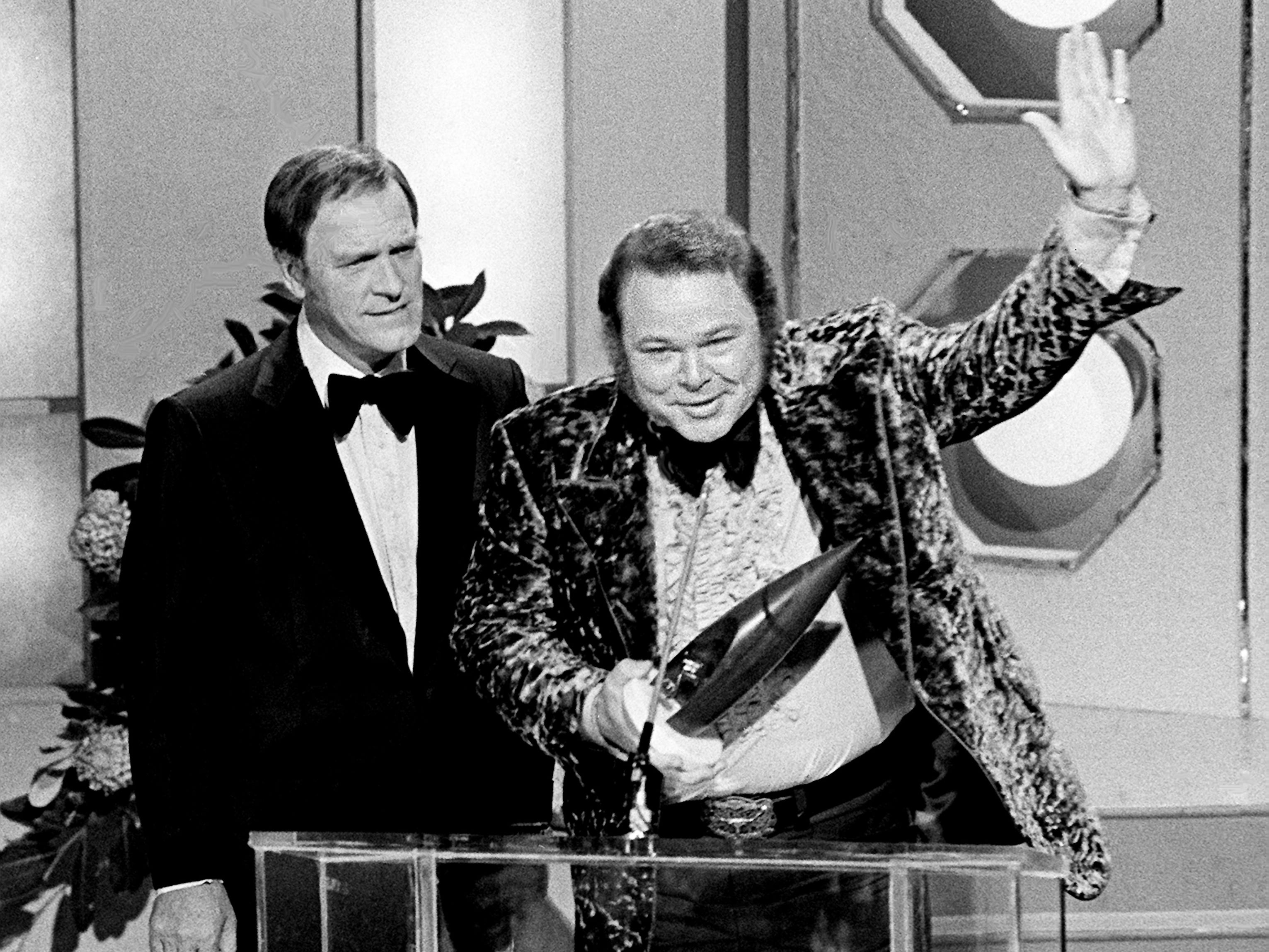 Roy Clark, right, accepts the coveted Entertainer of the Year award at the seventh annual CMA Awards show at the Grand Ole Opry House on Oct. 15, 1973. Looking on is presenter Eddy Arnold.