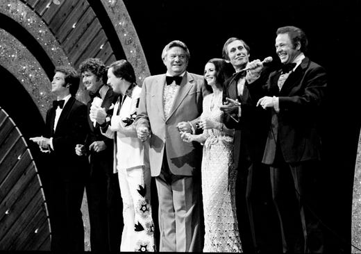 Roy Clark, right, is joined by Larry Gatlin, left, Mac Davis, Danny Davis, Jerry Clower, June Carter and Chet Atkins for a performance during the 11th annual CMA Awards show at the Grand Ole Opry House on Oct. 10, 1977.