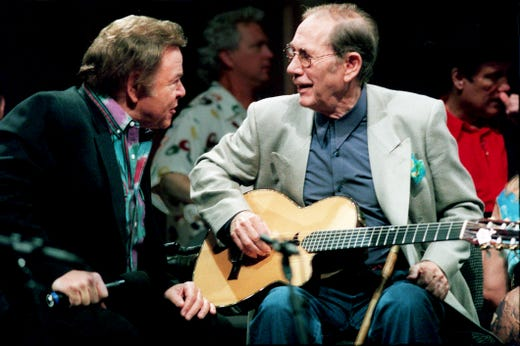 "Roy Clark, left, and Chet Atkins share a moment before a taping May 26, 1999, for the ""Ryman Country Homecoming,"" a three-part special slated for TNN."