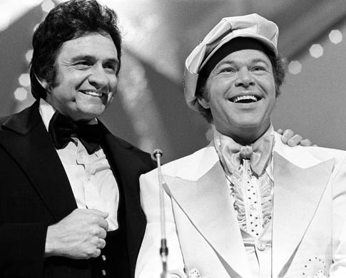 Co-hosts Johnny Cash, left, and Roy Clark say goodnight at the end of the CMA Awards show at the Grand Ole Opry House on Oct. 11, 1976.