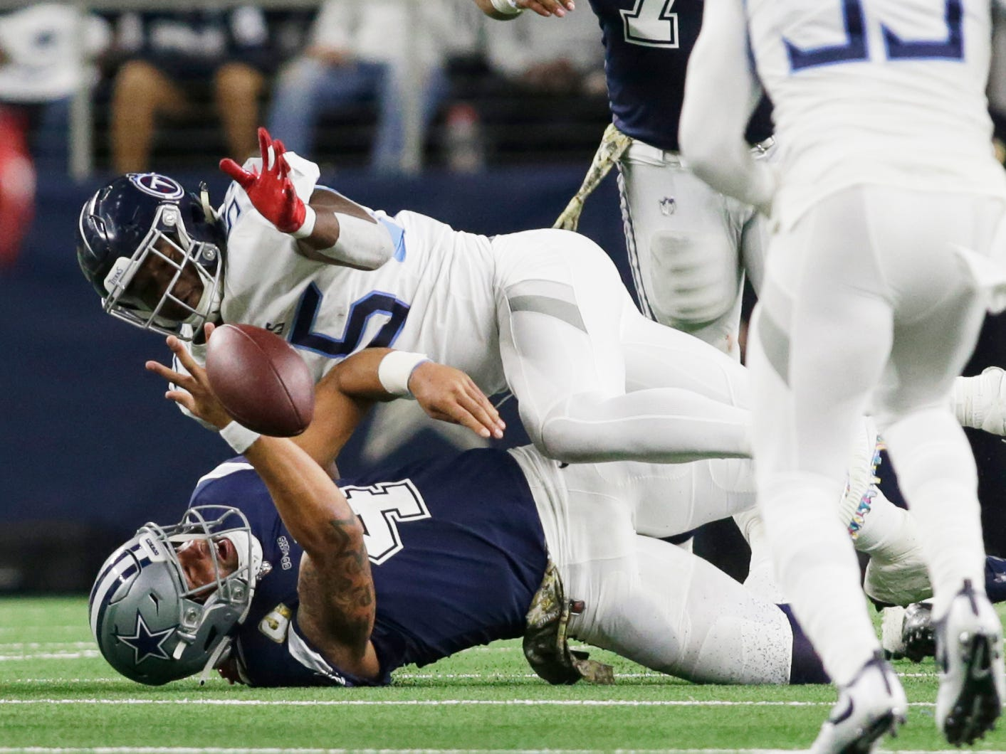 Dallas Cowboys quarterback Dak Prescott (4) fumbles after being tackled by Tennessee Titans inside linebacker Jayon Brown (55) in the third quarter at AT&T Stadium.