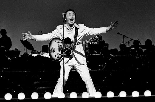 "Roy Clark finishes a song during the taping of ""The Grand Ole Opry at 50, A Nashville Celebration"" for a nationally televised special at the Opry House on Oct. 23, 1975."