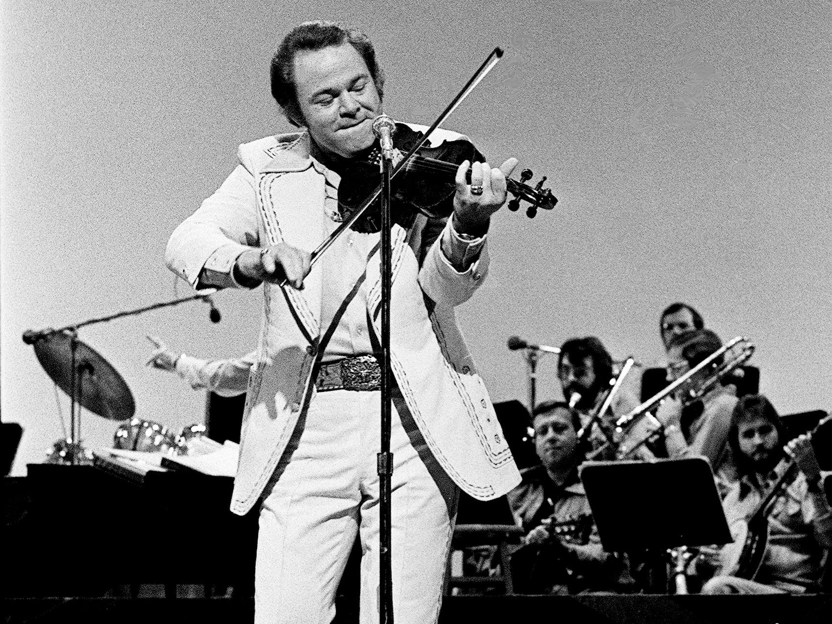 "Roy Clark shows off his fiddle skills during the taping of ""The Grand Ole Opry at 50, A Nashville Celebration"" for a nationally televised special at the Opry House on Oct. 23, 1975."