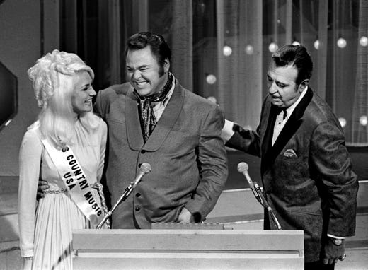 Presenter Roy Clark, center, makes eyes at Miss Country Music, a hostess, while master of ceremonies Tennessee Ernie Ford attempts to move Clark along during the CMA Awards show Oct. 25, 1969.