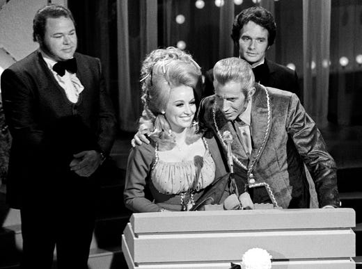Dolly Parton and Porter Wagoner, center, speak to the audience after winning the Duet Group of the Year award during the CMA Awards show at the Ryman Auditorium on Oct. 10, 1971. Looking on are presenters Roy Clark, left, and Merle Haggard.