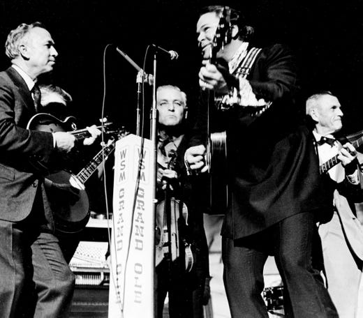 Roy Clark, second from right, and family make their strings sing Dec. 10, 1972, in a surprise performance at the Grand Ole Opry. Playing the mandolin, left, is Uncle Dudley, while Uncle Paul waits poised with his fiddle and Roy and his father, Hester, right, work on their guitars.