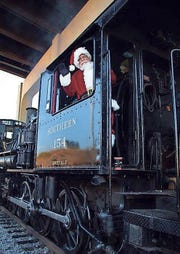 Santa gives a wave from the Christmas Lantern Express.
