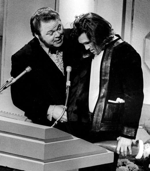 Appearing almost overcome with his Song of the Year award, Kris Kristofferson nervously tries to get his distance on the microphone offered by presenter Roy Clark during the CMA Awards show Oct. 14, 1970.