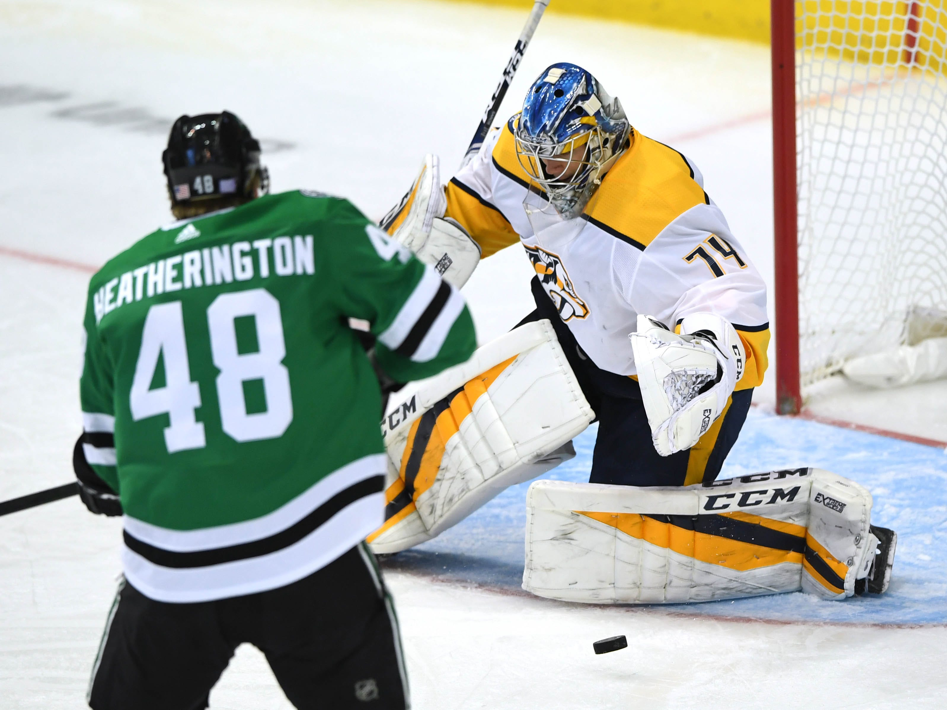 Nashville Predators goaltender Juuse Saros (74) makes a save as Dallas Stars defenseman Dillon Heatherington (48) looks on during the third period at American Airlines Center.