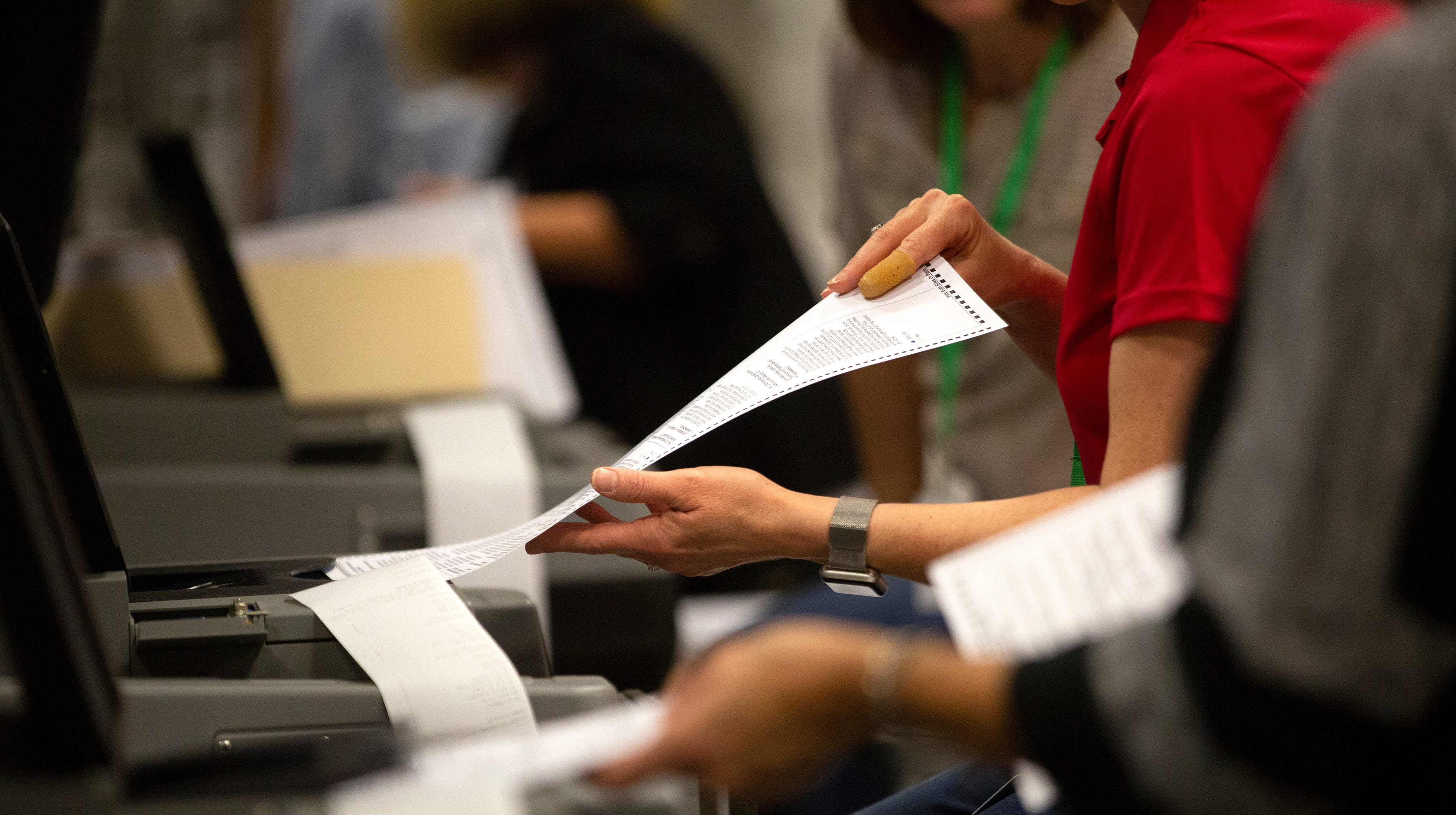 Election workers feed ballots in to voting machines, during an election recount at Monday, Nov. 12, 2018 in Naples, Florida.