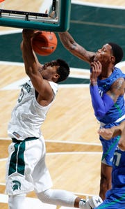 Florida Gulf Coast's Troy Baxter Jr., right, blocks a shot by Michigan State's Xavier Tillman during the first half Sunday in East Lansing, Mich.