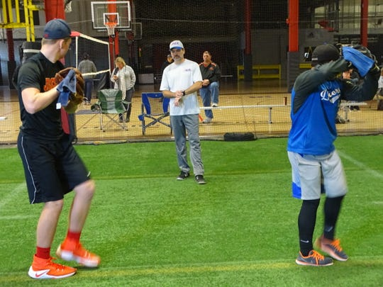 Lou Kolasky, of Rubber City Baseball Academy, oversees Mount Vernon junior Will Small and Danbury sophomore Aerion Gipson participating in a balance drill Sunday during the National Pitching Association Great Lakes Super Camp at Total Athletic Development.