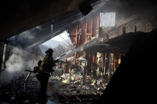 Capt. Adrian Murrieta with the Los Angeles County Fire Dept., hoses down hot spots on a wildfire-ravaged home Saturday, Nov. 10, 2018, in Malibu, Calif. Scores of houses from ranch homes to celebrities' mansions burned in a pair of wildfires that stretched across more than 100 square miles of Southern California, authorities said Saturday.