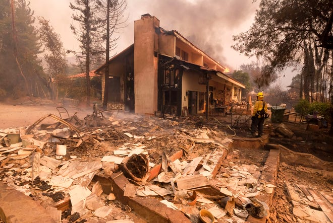 A firefighter keeps watch as the charred remains of a burned out home are seen during the Woolsey Fire in Malibu, Calif., Friday, Nov. 9, 2018.