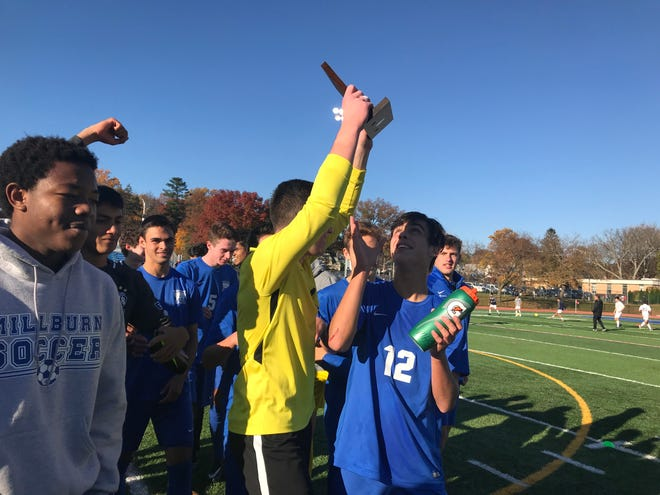 Millburn goalie Zach Barr (yellow) celebrates with the sectional championship trophy.