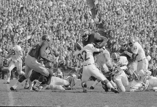 Halfback Ron Johnson of Michigan is stopped after a short third period gain by Michigan State defensive back Bill Ware in Ann Arbor, Mich., Oct. 14, 1967.  (AP Photo/Preston Stroup)