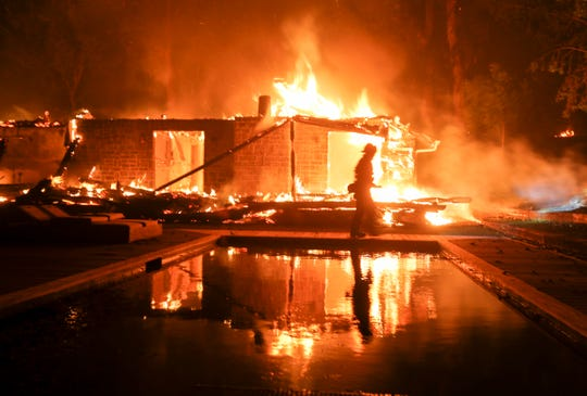 A firefighter walks by the a burning home in Malibu, Calif., Friday, Nov. 9, 2018. A Southern California wildfire continues to burn homes as it runs toward the sea. Winds are blamed for pushing the fire through scenic canyon communities and ridgetop homes.
