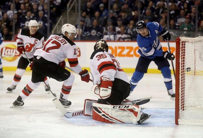 Winnipeg Jets' Mark Scheifele (55) scores on New Jersey Devils goaltender Cory Schneider (35) during second period NHL hockey action in Winnipeg, Manitoba, Sunday, Nov. 11, 2018.