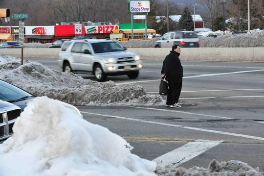 A 2011 file photograph at the intersection of Route 23 and Kiel Avenue in Butler which is a perilous crossing for pedestrians. A Pedestrian gets pushed to the edge while trying to cross Route 23 safely, despite not being able to use the crosswalks because of snow.