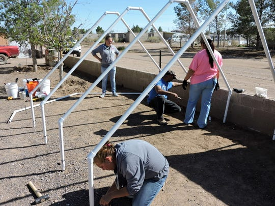A group of volunteers help to assemble a greenhouse at the home of a Palomas resident. Health Promoters provide home gardeners seeds, supplies and gardening advice to help them grow fresh produce for their families. Several schools have also been provided with greenhouses where children learn to grow their own food. The resulting vegetables are used in school lunches.
