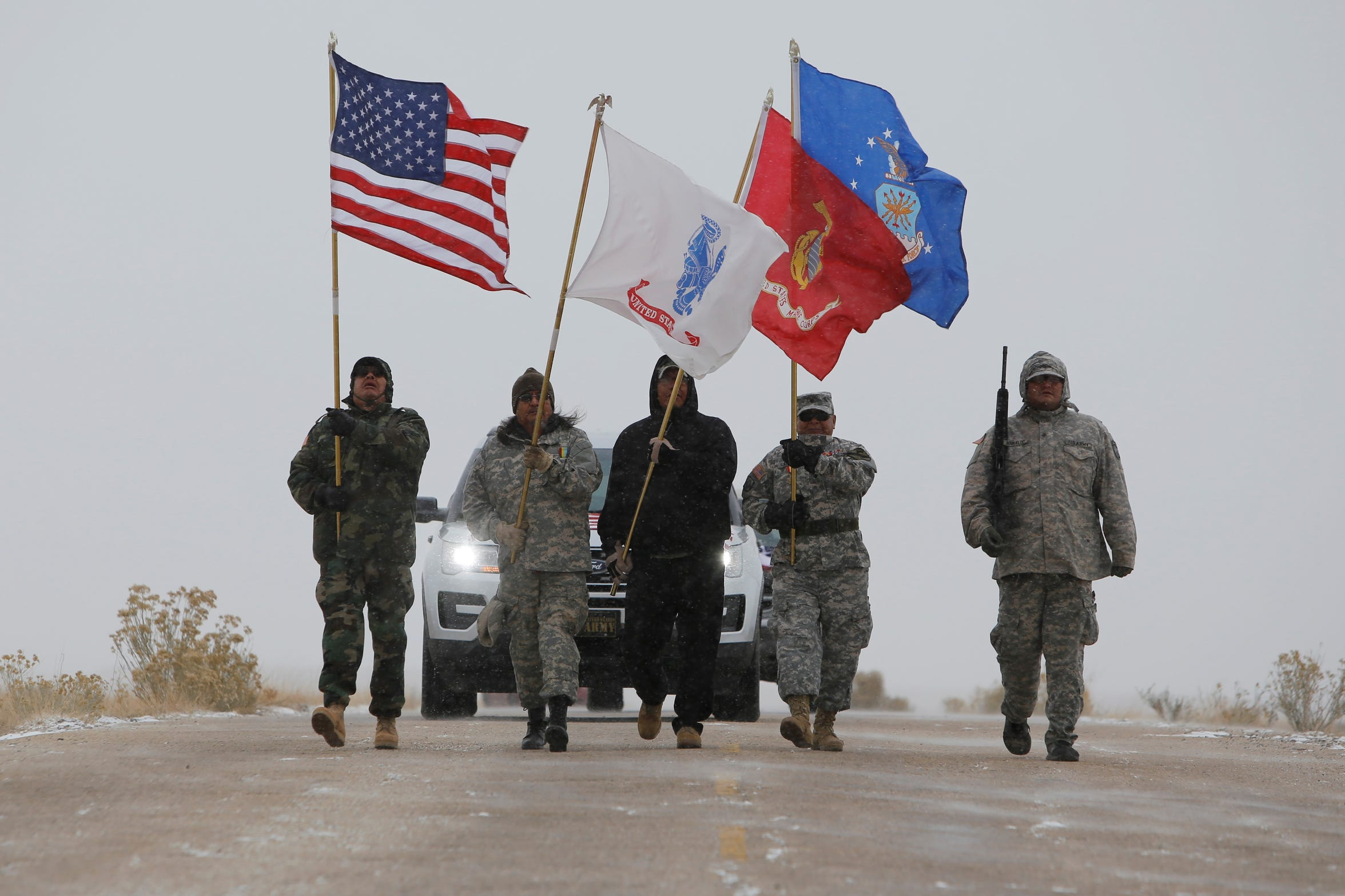 Members of the Tooh Haltsooí Veterans Organization carry flags in the Veterans Day parade on Monday in Sheep Springs.