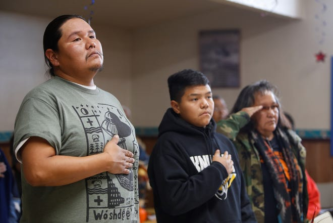 Tsé Alnaozt'i'í Chapter residents Elton Brown, Jacey Brown and Elouise Brown, from left, stand for the national anthem during the Veterans Day event on Monday at the Tooh Haltsooí Chapter house in Sheep Springs.