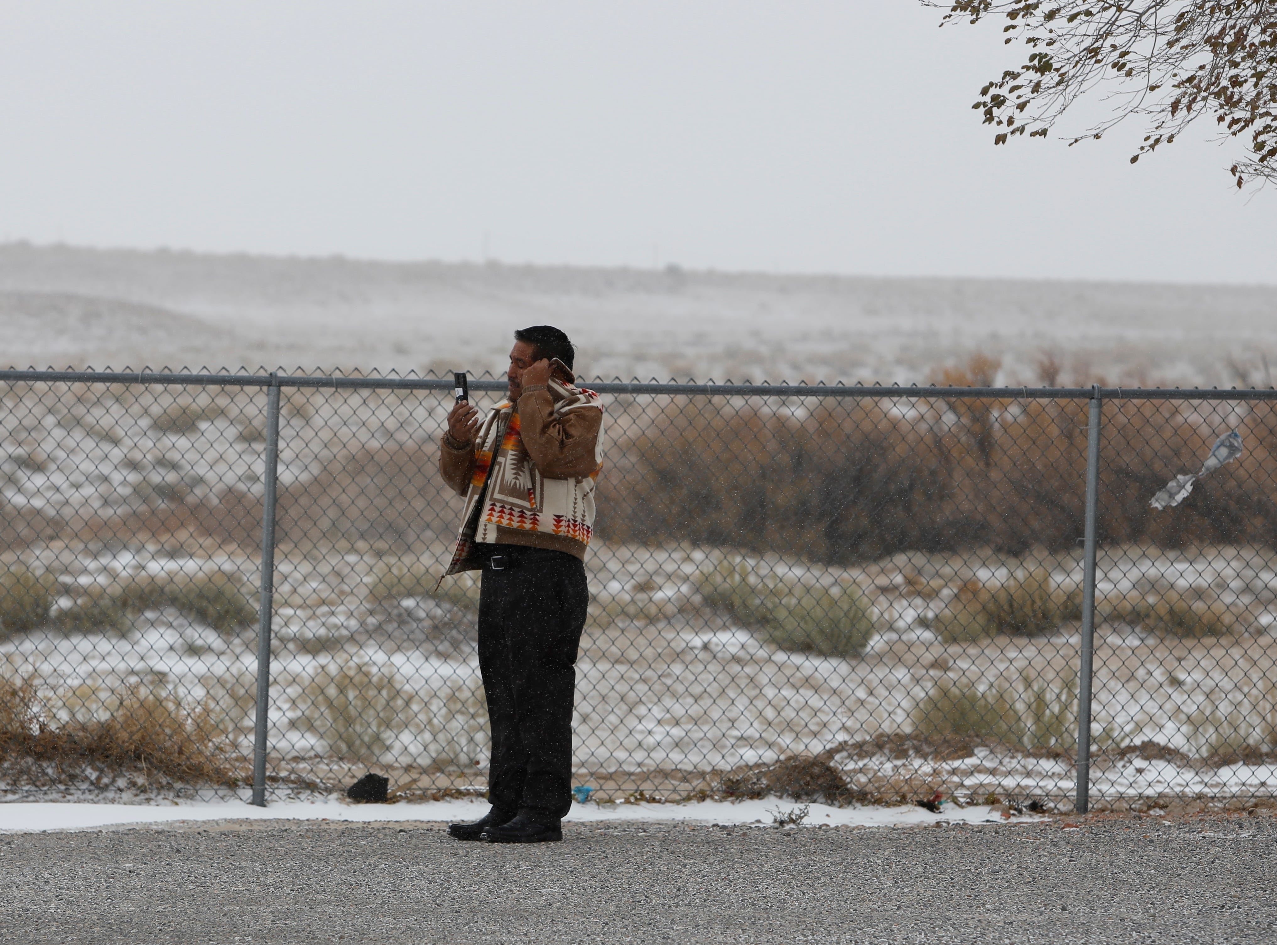 Tooh Haltsooí Chapter Manager Kevin Begay watches the Veterans Day parade as it proceeds to the chapter house on Monday.