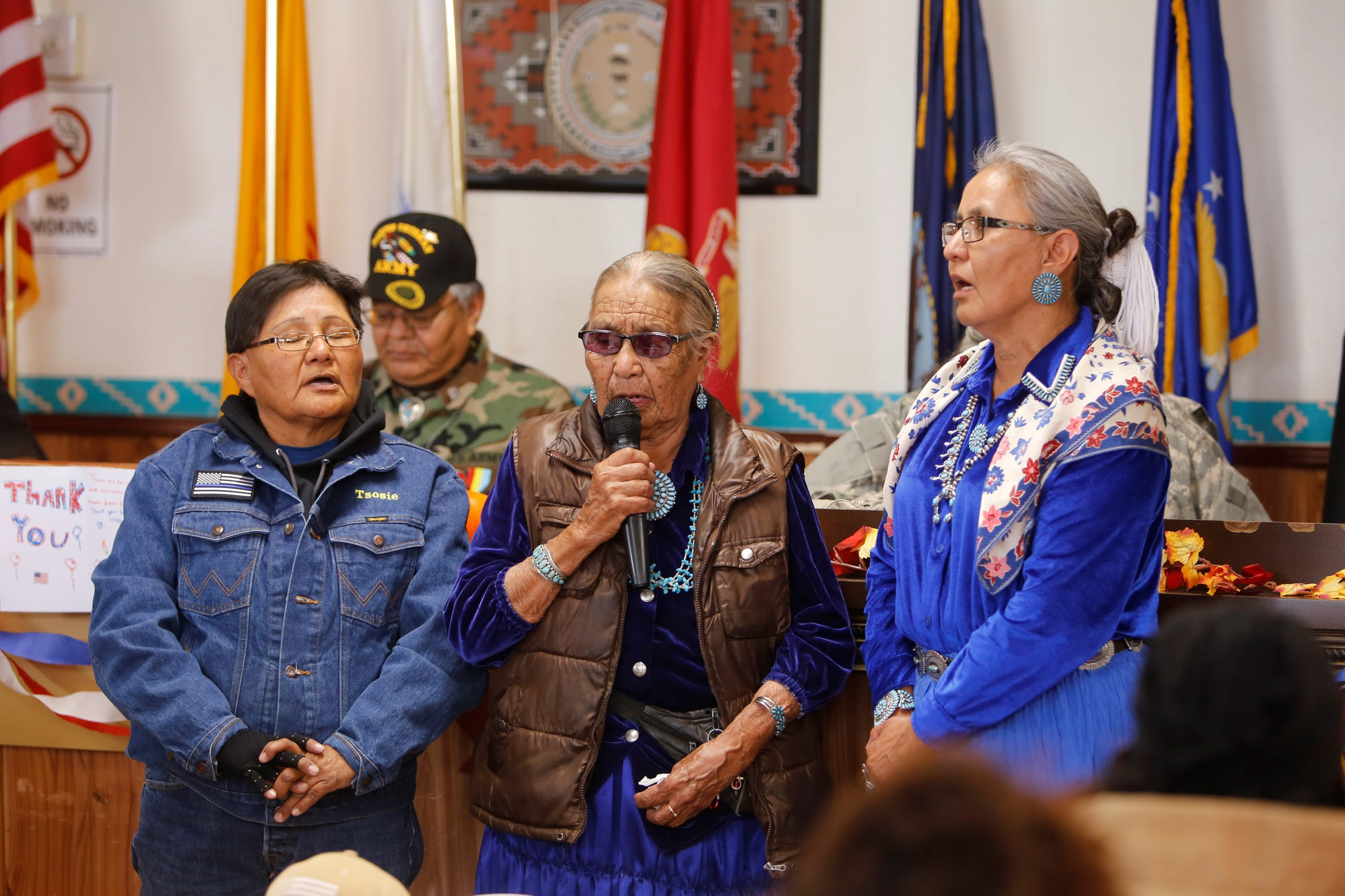 """Bessie Tsosie, Mary Attakai Tsosie and Arlene Tsosie, from left, sing """"Amazing Grace"""" in the Navajo language at the Veterans Day event on Monday at the Tooh Haltsooí Chapter house in Sheep Springs."""
