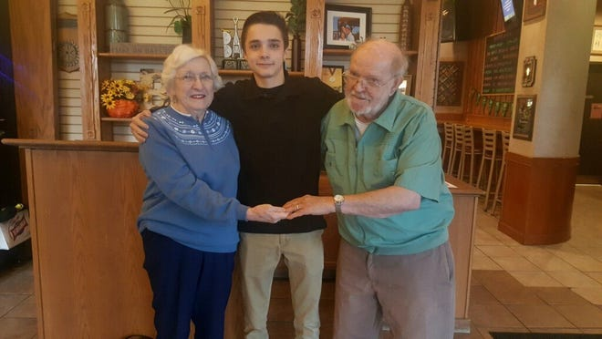 Mary Alice Luther and Ben Luther stand with Baker's of Milford busboy Max Poser after thanking him for finding and returning his wedding ring, which he lost at the restaurant.