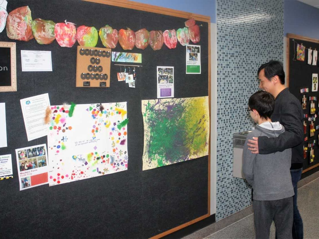 Orson Wang and his son Jasper check out artwork that decorates the walls of the renovated school