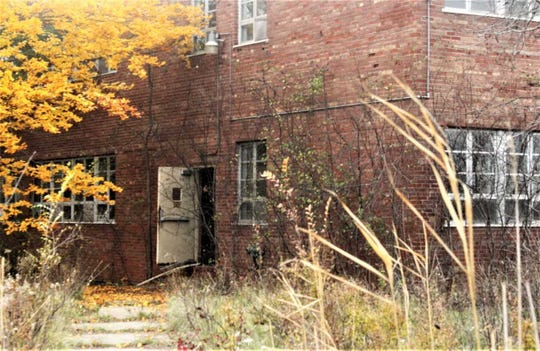 A door is propped open on one of the outlying buildings at the former state psychiatric site.