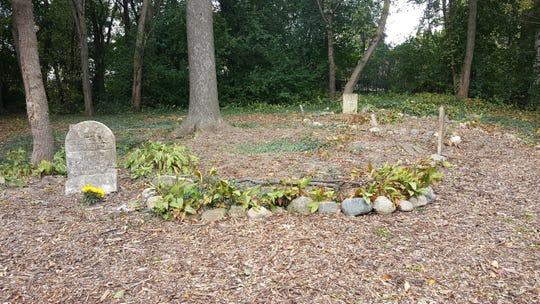 The inconspicuous Shearer Cemetery in Plymouth is now a tree-covered area that includes native plants, mulch paths and benches, thanks to the work of a local high school teacher and his students.