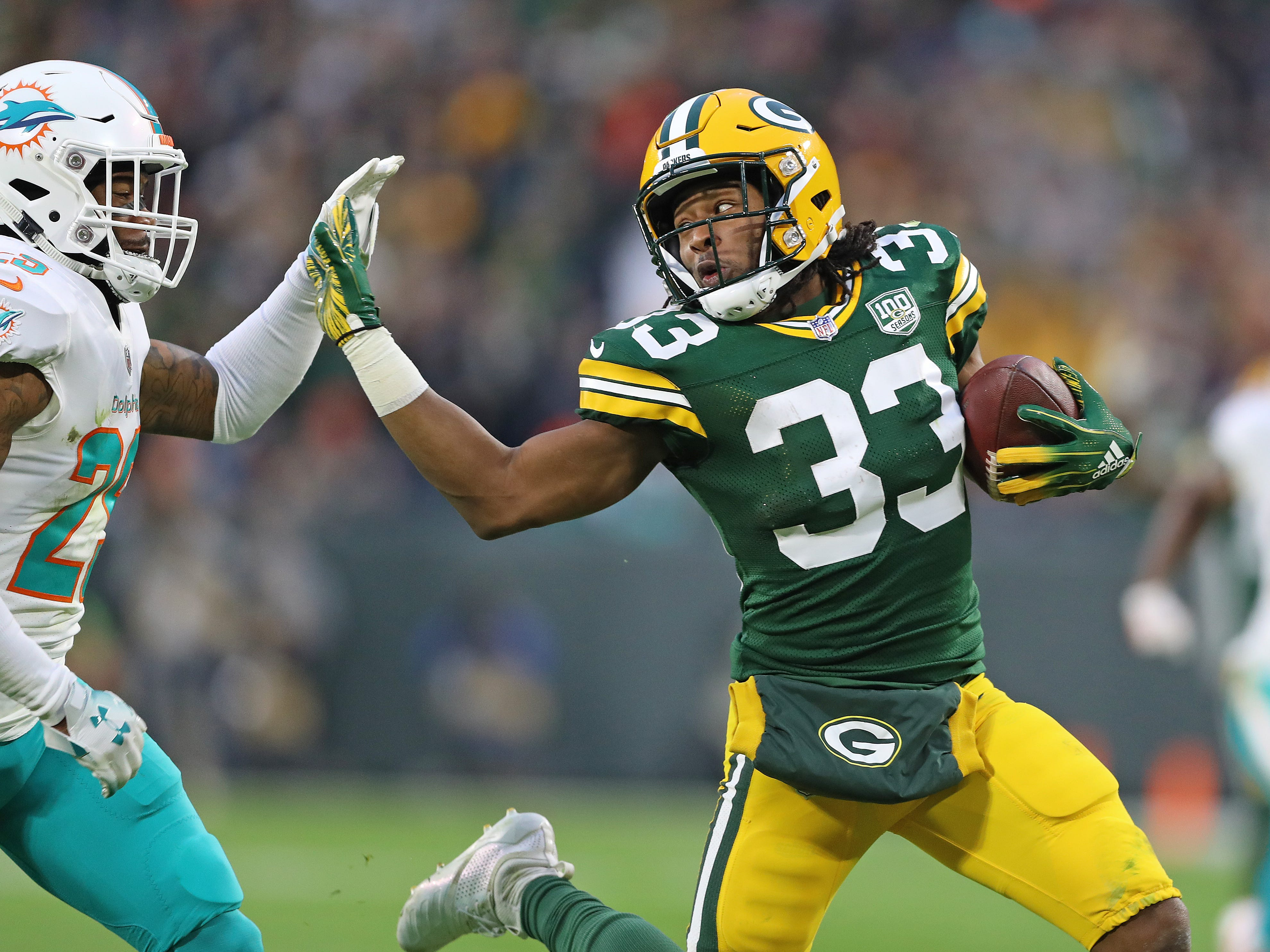 Green Bay Packers running back Aaron Jones (33) fends off a tackler against the Miami Dolphins at Lambeau Field Sunday, November 11, 2018 in Green Bay, Wis. Jim Matthews/USA TODAY NETWORK-Wis