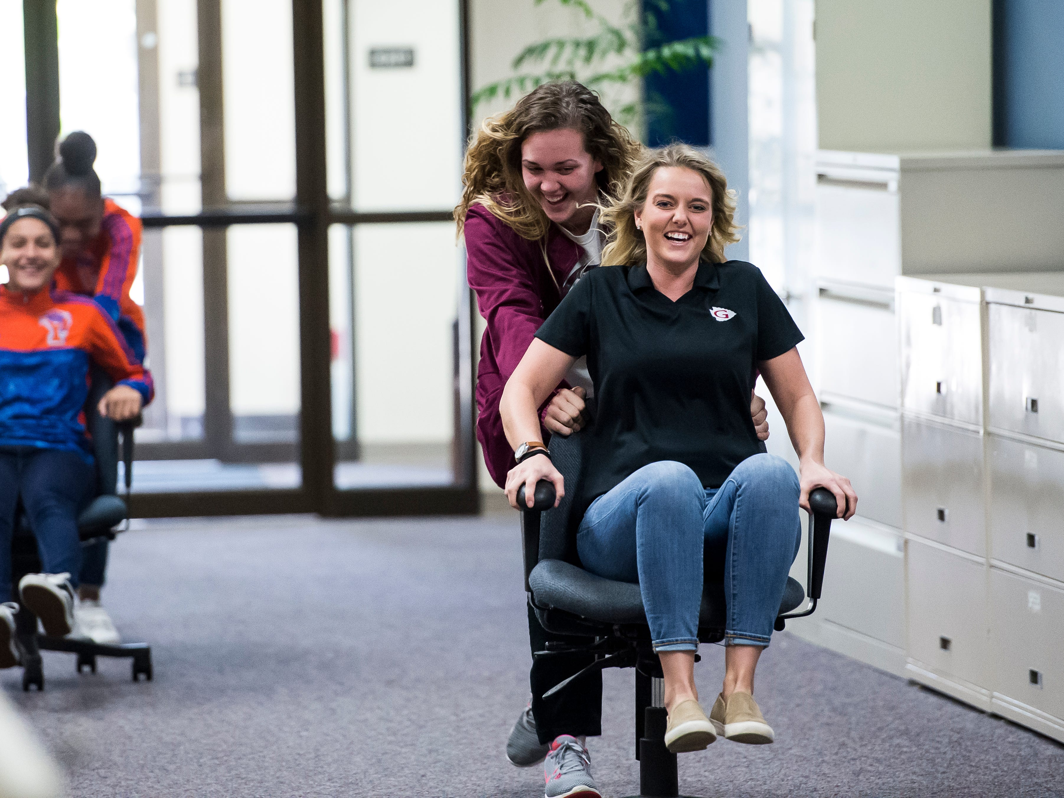 Gettysburg Area High School basketball player Taylor Richardson pushes coach Lauren Nell during an office chair race at the GameTimePa winter sports media day in York on Sunday, November 11, 2018.