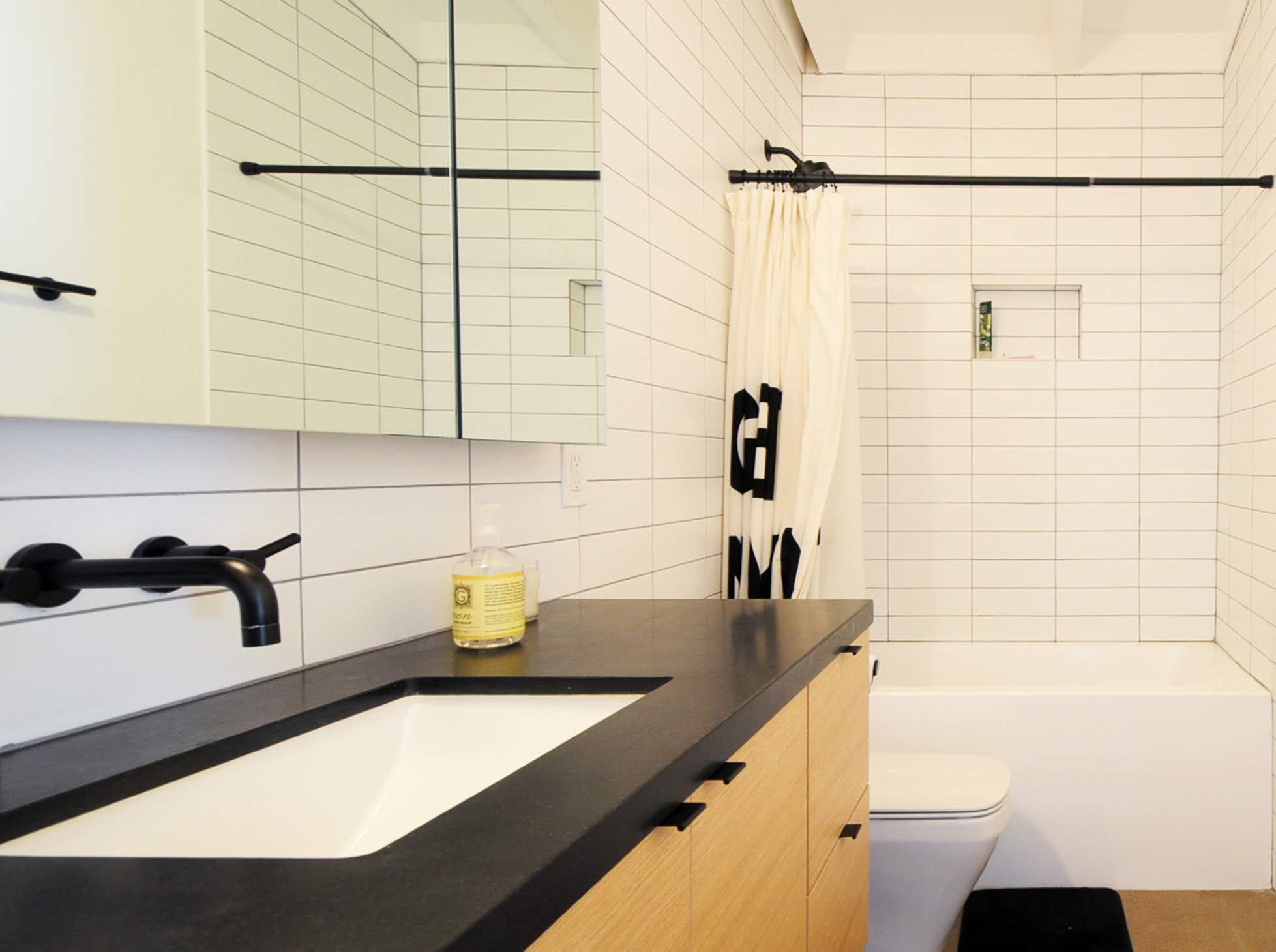 White tile mixes with a black countertop and fixtures to create a clean aesthetic in the home's second bathroom.