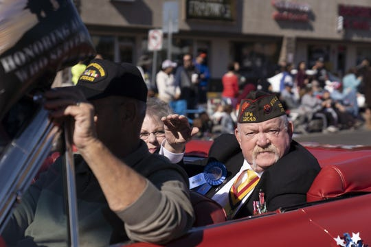 Gene Wood, 68, a Vietnam and Desert Storm veteran, waves at the crowd during the Veterans Day Parade in Phoenix on Nov. 12, 2018.