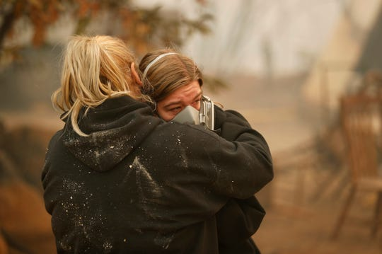 Krystin Harvey, left, comforts her daughter Araya Cipollini at the remains of their home burned in the Camp Fire, Nov. 10, 2018, in Paradise, California. The blaze that started Thursday outside the hilly town of Paradise has grown and destroyed more than 6,700 buildings, almost all of them homes.