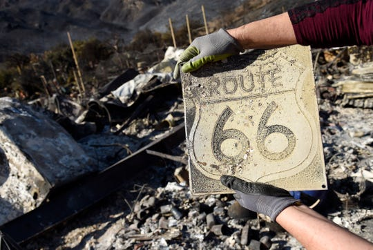 Donna Phillips shows a charred Route 66 sign she found among the possessions of her friend Marsha Maus, Nov. 11, 2018, after wildfires tore through the Seminole Springs Mobile Home Park in Agoura Hills, California. Maus has been a resident of the neighborhood for 15 years.