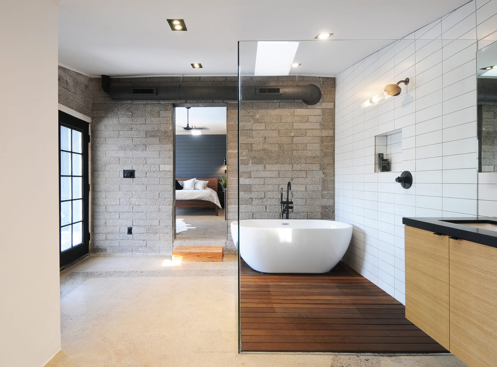 The master bathroom combines a mixture of teak, white tile, concrete floor, block walls and black-framed French doors.