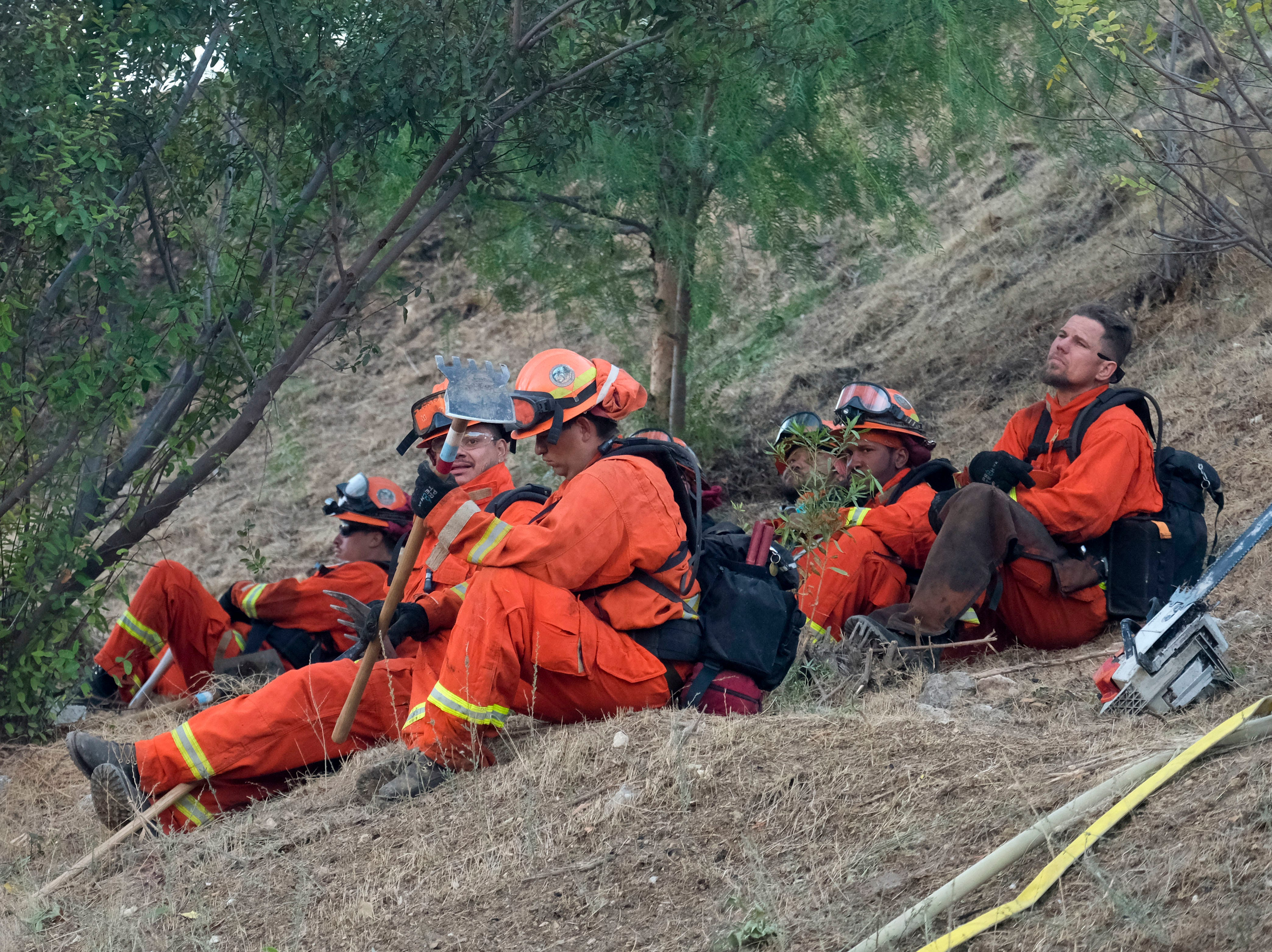 Members of a hand crew rest on a hillside in West Hills, California, Nov. 11, 2018.