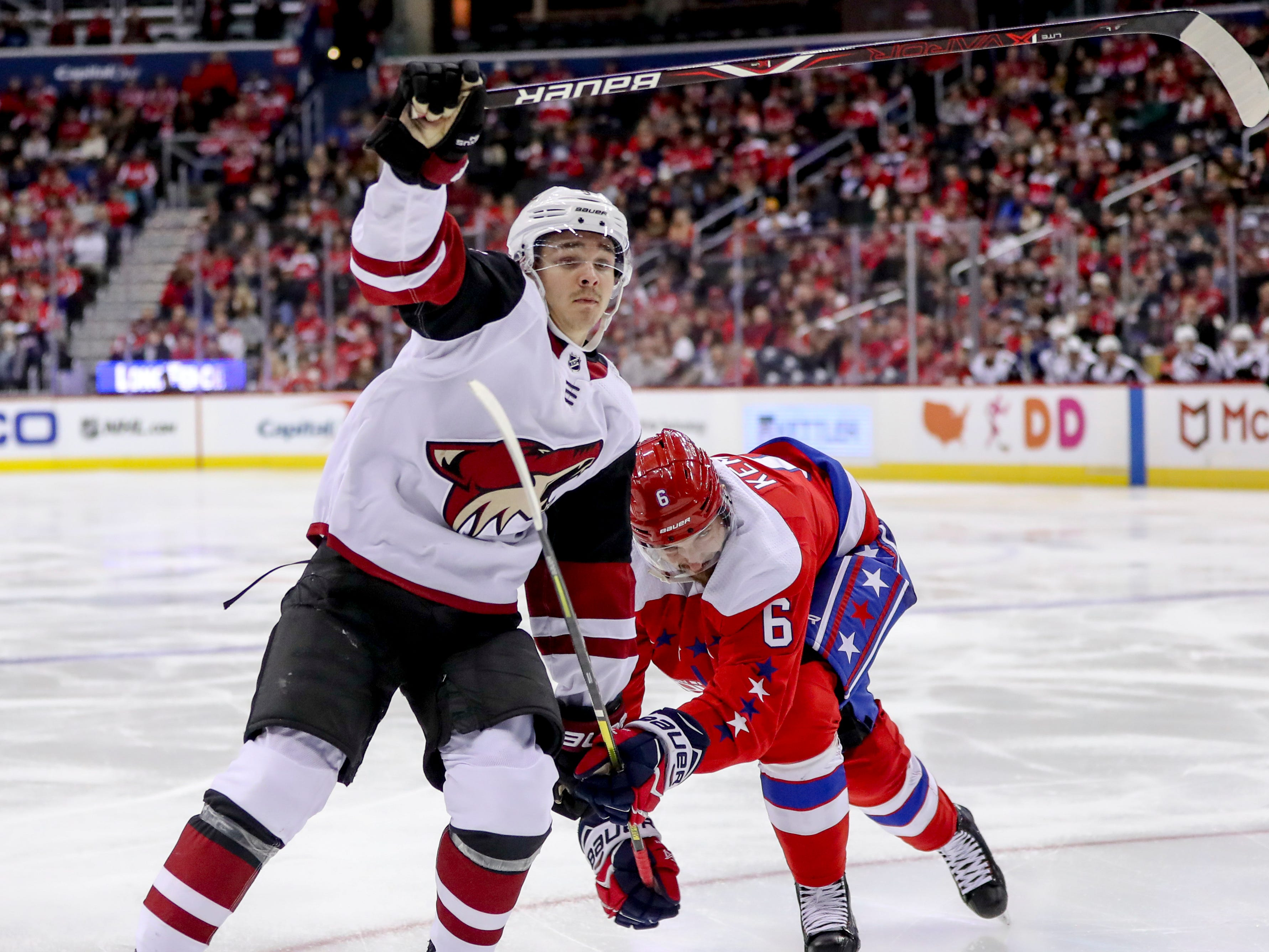 Arizona Coyotes center Clayton Keller and Washington Capitals defenseman Michal Kempny fight for a lose puck in the third period of an NHL hockey game, Sunday, Nov. 11, 2018 in Washington. The Coyotes won 4-1. (AP Photo/Andrew Harnik)