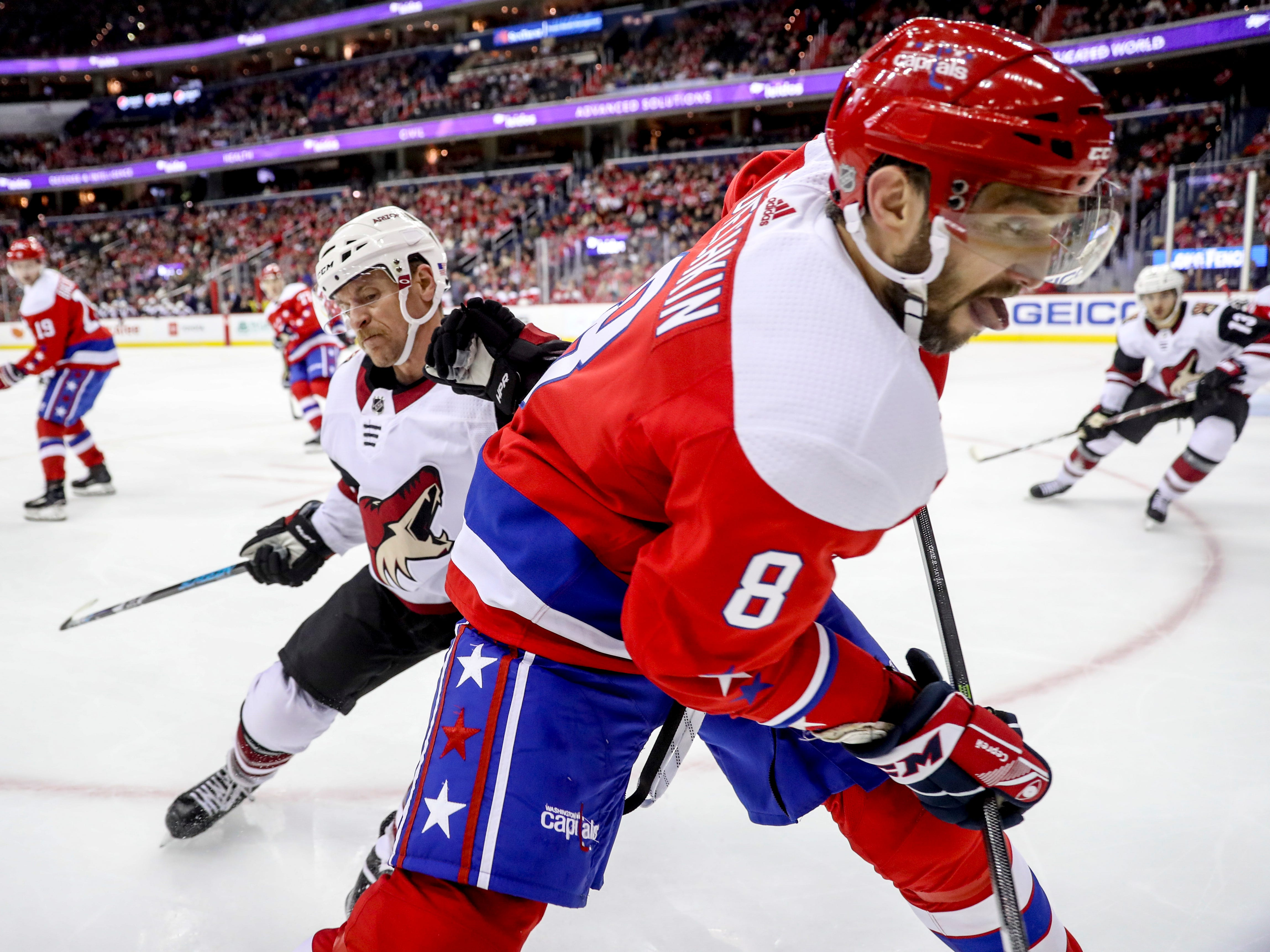 Arizona Coyotes right wing Michael Grabner, back, and Washington Capitals left wing Alex Ovechkin (8) battle for the puck in the third period of an NHL hockey game, Sunday, Nov. 11, 2018, in Washington. (AP Photo/Andrew Harnik)
