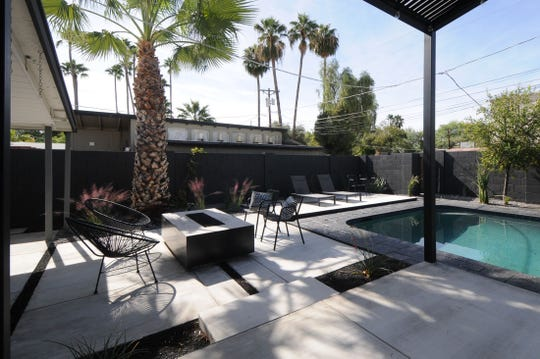 Black is featured prominently in the home's backyard, too, with lava rock, a steel shade structure and tile that encircles the pool.
