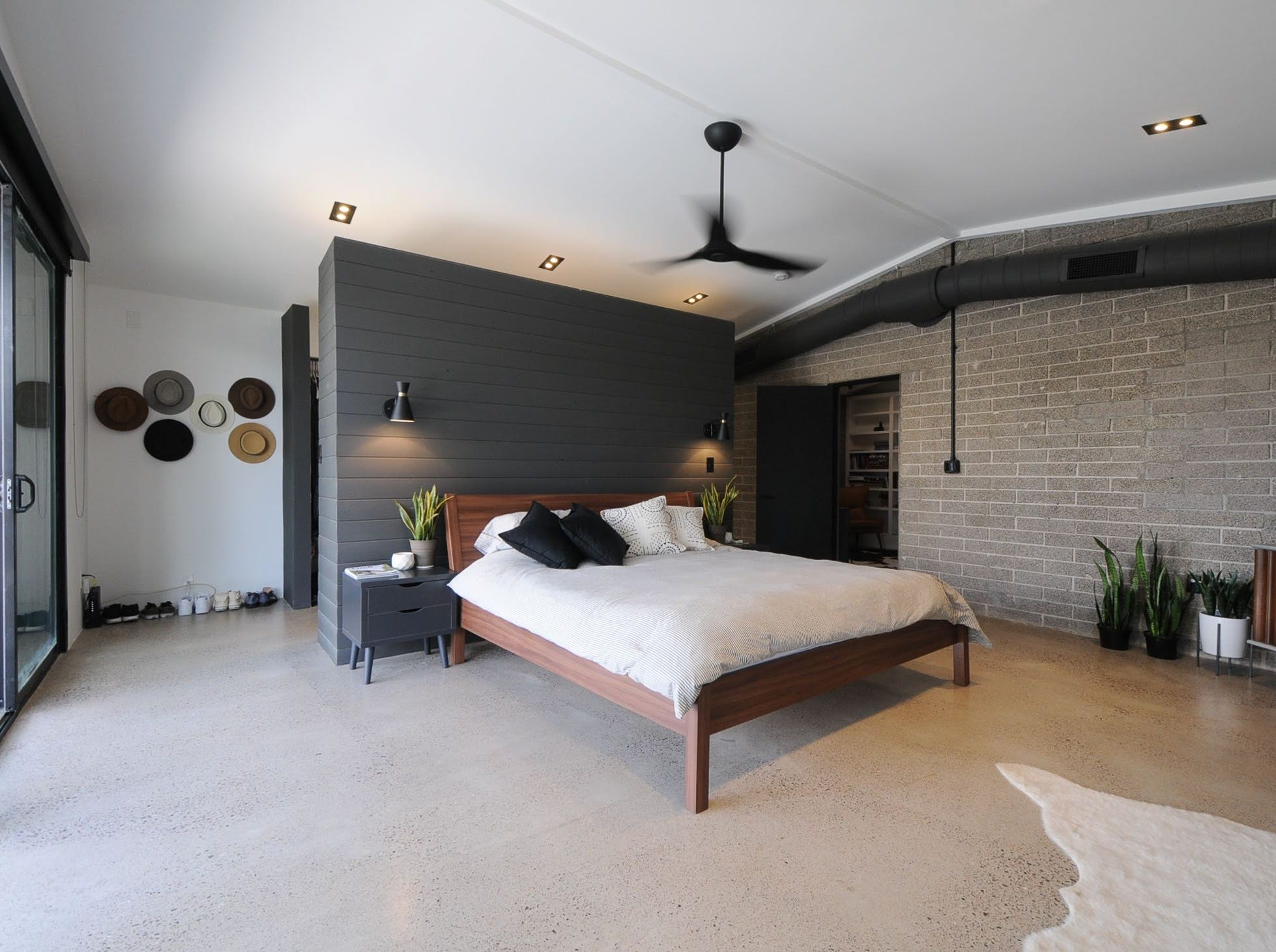 Gwilliam and Peterson's master bedroom looks nothing like the woodshed the structure once was, and instead gives an industrial feel with its concrete floors and block walls.