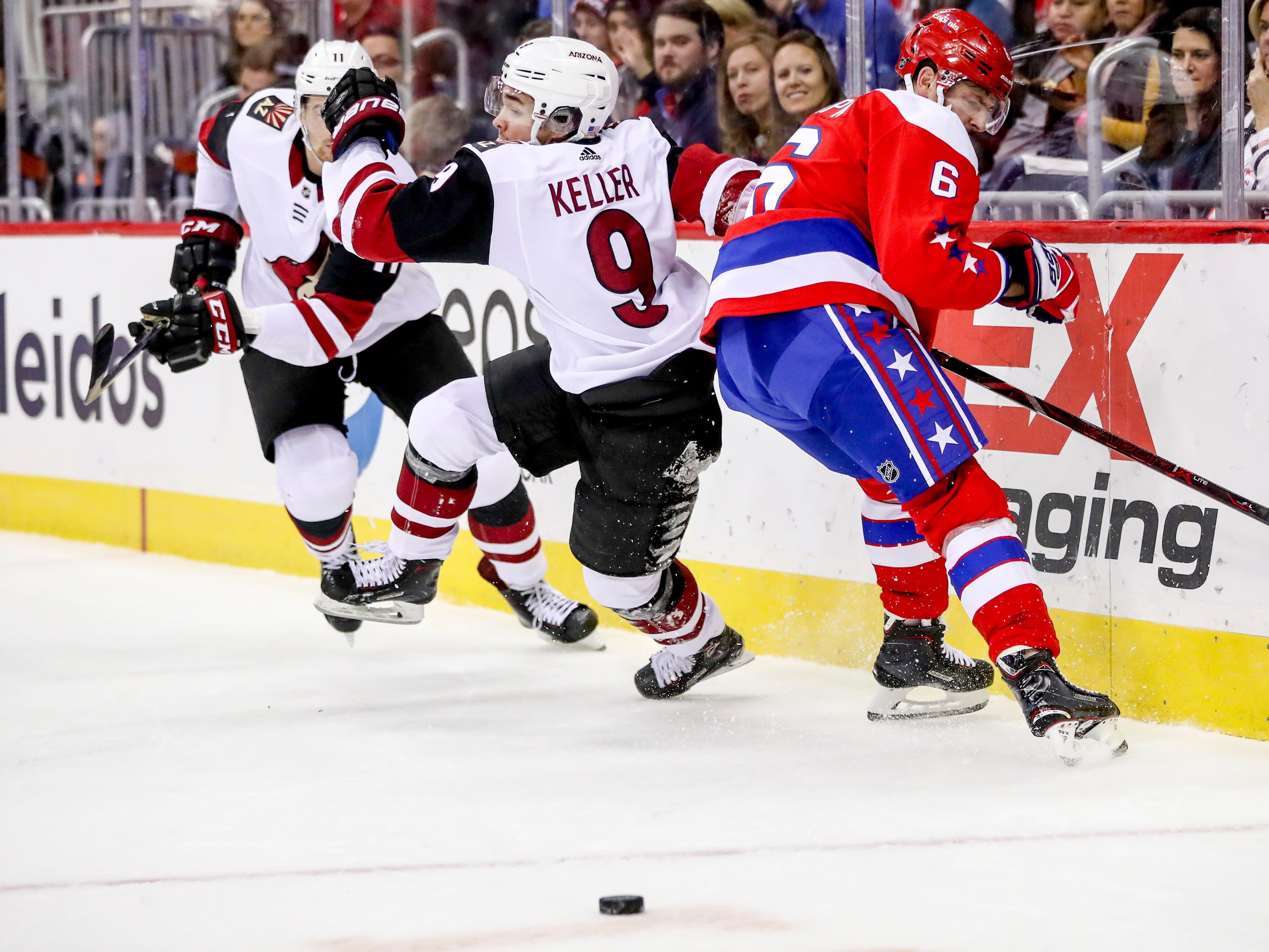 Washington Capitals defenseman Michal Kempny takes down Arizona Coyotes center Clayton Keller as they fight for a lose puck in the first period of an NHL hockey game between the Washington Capitals and the Arizona Coyotes, Sunday, Nov. 11, 2018 in Washington. (AP Photo/Andrew Harnik)