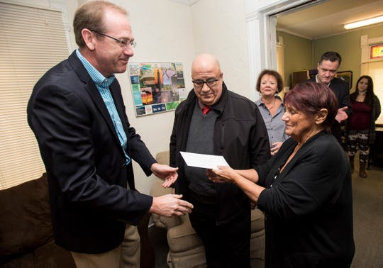 Comprehensive Youth Services CEO Jeffrey Oldham, center, watches as Community Foundation Chairman Mike Cansfield, left, hands the deed to the Wings house to The Harbor Program Director Sally Currie Monday, Nov. 12, 2018 at the Harbor in Port Huron.